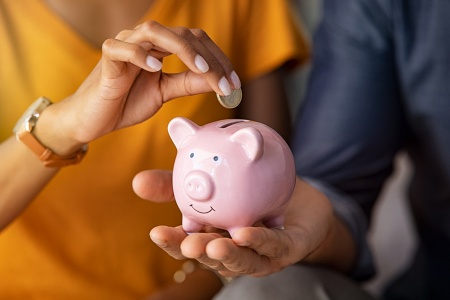 A couple depositing money into a piggy bank for an emergency fund.